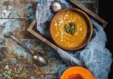 Schüssel traditionelle selbst gemachte Kürbissuppe mit seads, Creme und Brot auf rustikalem Holztisch Lizenzfreie Stockfotografie