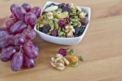Schüssel trockene Samen, Nüsse und rote Trauben auf Tabelle Lizenzfreies Stockfoto