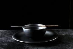 Schüssel und Ess-Stäbchen auf einer Platte Stockbild