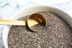Schüssel und Schaufel mit chia Samen auf Tabelle lizenzfreie stockfotografie