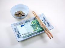 Schüssel und Teller voll von Euro mit Ess-Stäbchen stockbild