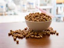 Schüssel verschüttete Erdnüsse auf Holzoberfläche mit sonnigem Hintergrund Lizenzfreies Stockfoto