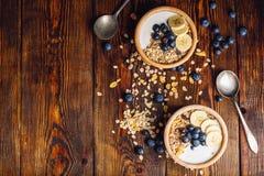 Schüssel zwei mit des Granolas, der Banane und der Blaubeere Lizenzfreies Stockfoto