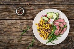 Schüsselmittagessen mit gegrilltem Rindfleischsteak und -quinoa, Mais, Gurke, Rettich und Arugula stockfotos