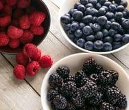 Schüsseln frische Frucht auf hölzernem Hintergrund stockbilder