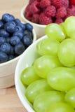 Schüsseln gesunde Trauben, Blaubeeren u. Himbeeren Stockfoto