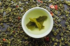 Schüsseln mit Blatt grünen oolong Tee und Erdbeeren Stockbilder