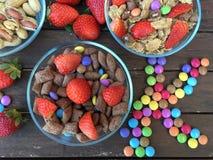 Schüsseln mit Flocken, Erdbeeren, Erdnüssen und farbiger Süßigkeit Lizenzfreie Stockbilder