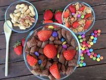 Schüsseln mit Flocken, Erdbeeren, Erdnüssen und farbiger Süßigkeit Stockbild