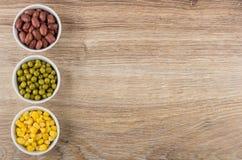 Schüsseln mit roten Bohnen, grünen Erbsen und Zuckermais Stockfotos