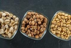 Schüsseln mit sortierten Nüssen mögen Haselnüsse Pistazie und Erdnüsse auf gesundem Lebenkonzept des schwarzen Schiefers Stockbilder