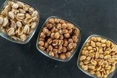 Schüsseln mit sortierten Nüssen mögen Haselnüsse Pistazie und Erdnüsse auf gesundem Lebenkonzept des schwarzen Schiefers Lizenzfreies Stockfoto