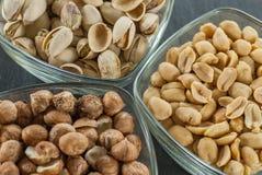 Schüsseln mit sortierten Nüssen mögen Haselnüsse Pistazie und Erdnüsse auf schwarzem Schiefer mit Kopie sperren gesundes Lebenkon Stockfotos