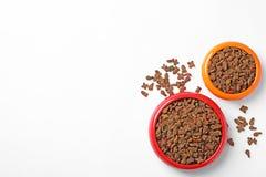 Schüsseln trockene Nahrung für Haustiere auf weißem Hintergrund stockfotos
