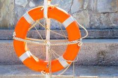 Schützen Sie Rettungsring mit einem Jutefaserseil am Steinhintergrund lizenzfreie stockbilder