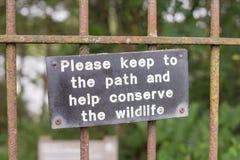 Schützen Sie Signage der wild lebenden Tiere auf dem Tor, das zu Waldbahn führt Lizenzfreies Stockfoto
