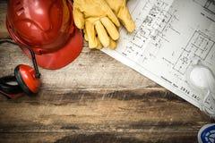 Schützende Arbeitskleidung des Baus mit Plänen Stockfoto