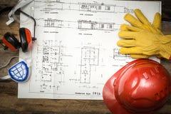 Schützende Arbeitskleidung des Baus mit Plänen Lizenzfreie Stockbilder
