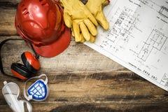 Schützende Arbeitskleidung des Baus mit Plänen Stockbild