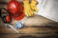 Schützende Arbeitskleidung des Baus mit Plänen Lizenzfreies Stockbild