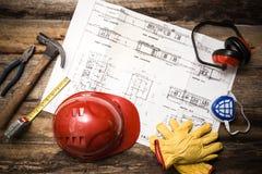 Schützende Arbeitskleidung des Baus mit Plänen Stockfotos