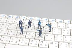 Schützende Laptop-Computer der Minipolizeigruppe Stockfotografie