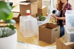 Schützender Vase der Frau mit Folie beim Verpacken des Materials in Kästen nach Verlegung stockfotografie