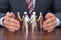 Schützendes Team des Geschäftsmannes von Papierleuten auf Schreibtisch Stockfotos