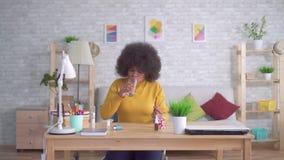 Sch?ne Afroamerikanerfrau mit einer Afrofrisur nimmt eine Pille und Getr?nke von einem Glas Wasser stock video