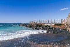 Sch?ne Ansicht h?lzerner Pier auf dem Ufer und den Steinen Die Welle n?hert sich dem Ufer stockfotos