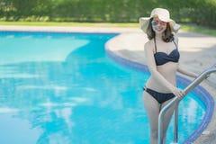 Sch?ne Asain-Frauen mit Bikini genie?en Sommerferien im Swimmingpool lizenzfreie stockbilder