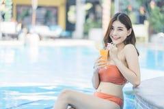 Sch?ne Asain-Frauen mit Bikini genie?en Sommerferien im Swimmingpool lizenzfreies stockfoto