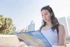 Sch?ne asiatische touristische Frau, welche die Karte sucht nach Besichtigungsstelle der Touristen betrachtet lizenzfreies stockfoto