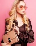 Sch?ne blonde Frau in einer Bluse und in Hosen, welche die Gl?ser, Handtasche halten tragen lizenzfreie stockbilder