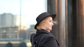 Sch?ne blonde junge Frau im L?cheln des schwarzen Hutes, das zur Kamera aufwirft, schaut aufw?rts gegen das Errichten der nahen A stock video