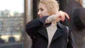 Sch?ne blonde junge Frau im L?cheln des schwarzen Hutes, das zur Kamera aufwirft, schaut aufw?rts gegen das Errichten der nahen A stock footage