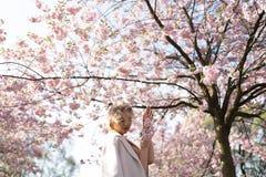 Sch?ne blonde junge Frau in Sakura Cherry Blossom-Park im Fr?hjahr Natur und Freizeit w?hrend sie genie?end reisend lizenzfreies stockbild