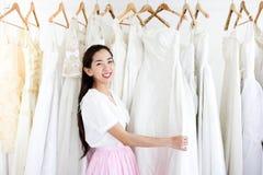 Sch?ne Braut, die durch ihren besten Freund in ihrem Hochzeitstag angekleidet erh?lt und ein Heiratskleid im Gesch?ft und im Gesc lizenzfreies stockfoto