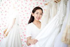Sch?ne Braut, die durch ihren besten Freund in ihrem Hochzeitstag angekleidet erh?lt und ein Heiratskleid im Gesch?ft und im Gesc lizenzfreie stockbilder