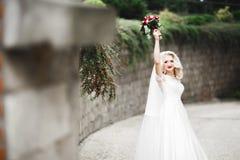 Sch?ne Braut im eleganten wei?en Kleid, das den Blumenstrau? aufwirft im Park h?lt stockbilder