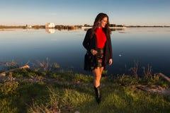 Sch?ne brunette Frauenportr?t-Stellungsau?enseite an einem sonnigen Tag, mit einem See im Hintergrund stockfotos