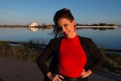 Sch?ne brunette Frauenportr?t-Stellungsau?enseite an einem sonnigen Tag, mit einem See im Hintergrund stockbilder