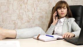 Sch?ne Gesch?ftsfrau, die im Stuhl mit blo?en F??en auf Tabelle sitzt M?dchen bei der Arbeit im B?ro am Telefon am Tisch und stock video