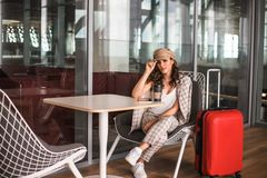 Sch?ne Gesch?ftsfrau mit der Tablette, die auf ihren Flug in einem Flughafen wartet lizenzfreie stockfotografie