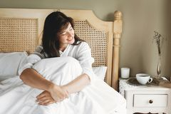 Sch?ne gl?ckliche junge Frau, die morgens im Bett im Hotelzimmer- oder Ausgangsschlafzimmer liegt Stilvolles brunette M?dchen in  stockbilder