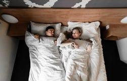 Sch?ne gl?ckliche junge Paare oder Familie, die zusammen im Bett aufwachen lizenzfreie stockfotos
