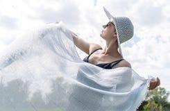 Sch?ne gl?ckliche kaukasische Frau, die einen Schal ?ber dem bew?lkten Himmel wellenartig bewegt stockfotos
