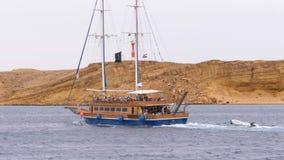 Sch?ne h?lzerne Yacht mit Touristen segelt in das st?rmische Meer auf dem Hintergrund von Felsen Egypt stock video
