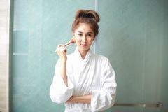 Sch?ne junge asiatische Frau im Bademantel, der Make-up anwendet stockfotografie