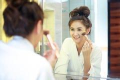 Sch?ne junge asiatische Frau im Bademantel, der Make-up anwendet stockfotos